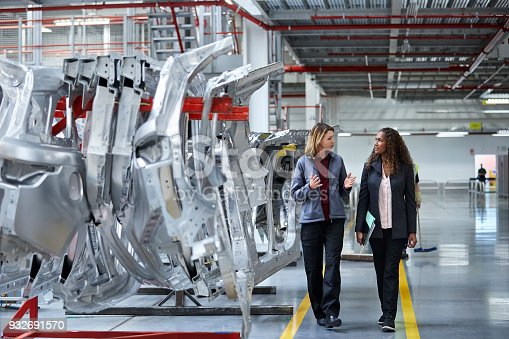 Female engineers discussing by car chassis. Full length of professionals are walking on aisle in factory. Colleagues are in automobile industry.