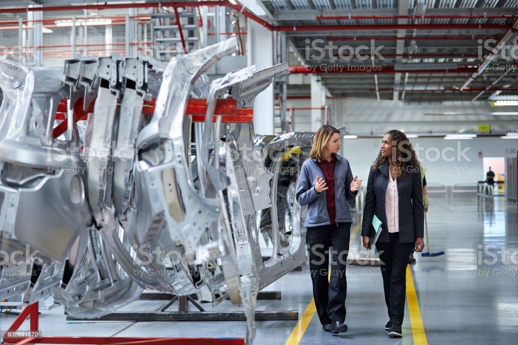 Ingenieure gehen während der Diskussion von Auto-chassis – Foto