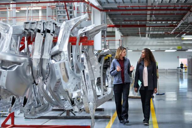 engineers walking while discussing by car chassis - pojazd mechaniczny zdjęcia i obrazy z banku zdjęć