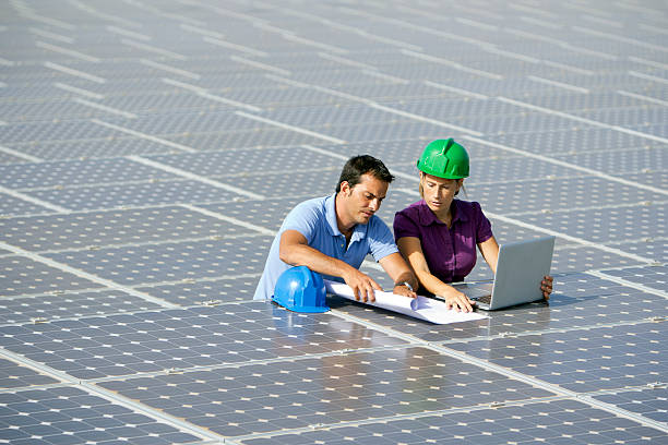 Engineers with blueprints Image of two engineers revising a photovoltaic farm (ISO 100). All my images have been processed in 16 Bits and transfer down to 8 before uploading. power occupation stock pictures, royalty-free photos & images