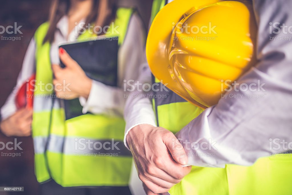 Engineers with helmet and tablet stock photo