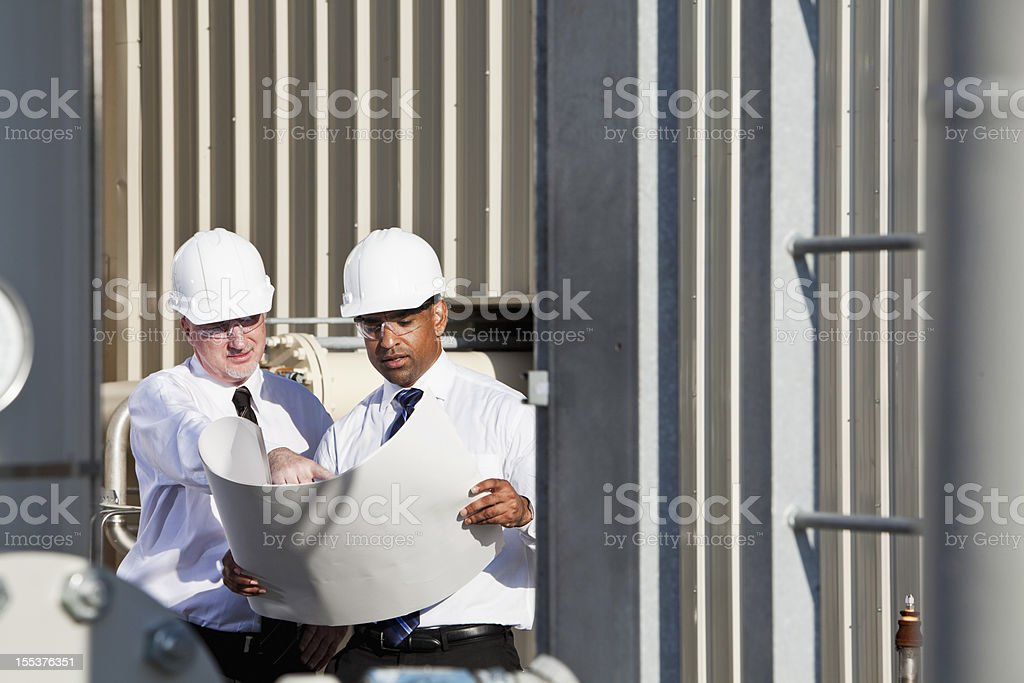 Engineers at industrial site with plans. .