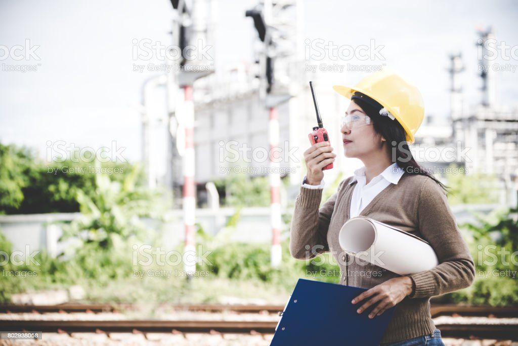 Engineers woman holding radio, blueprint and report schedule for workers security control at power plant energy industry. Engineer Concept stock photo