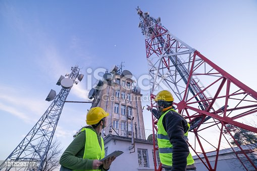 Engineers working on the field near a city Telecomunications tower, checking the condition of the Equipement. Technology and Global Business.