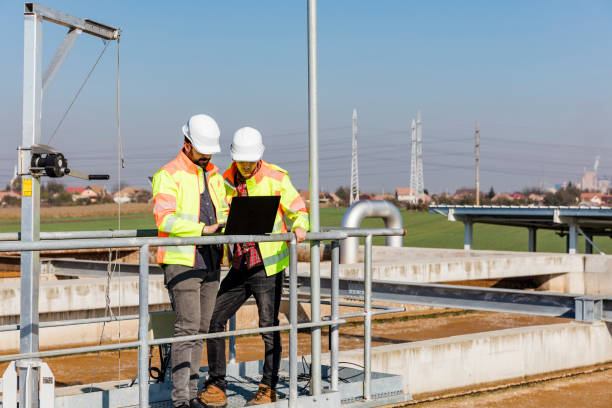 Engineers working on water treatment plant with laptop Engineers working on water treatment plant with laptop and measuring sensors sewage treatment plant stock pictures, royalty-free photos & images