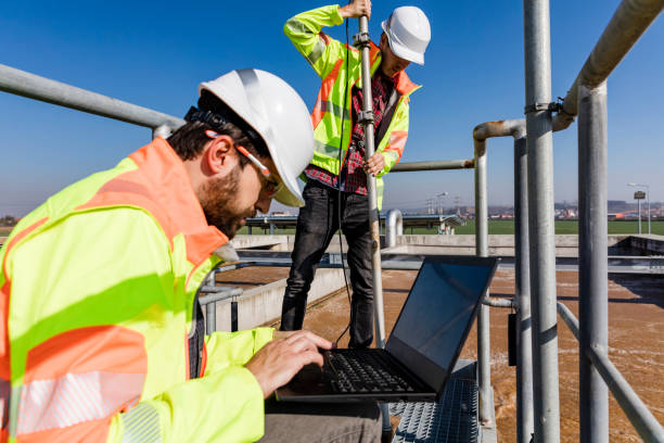 Engineers working on water treatment plant with laptop stock photo
