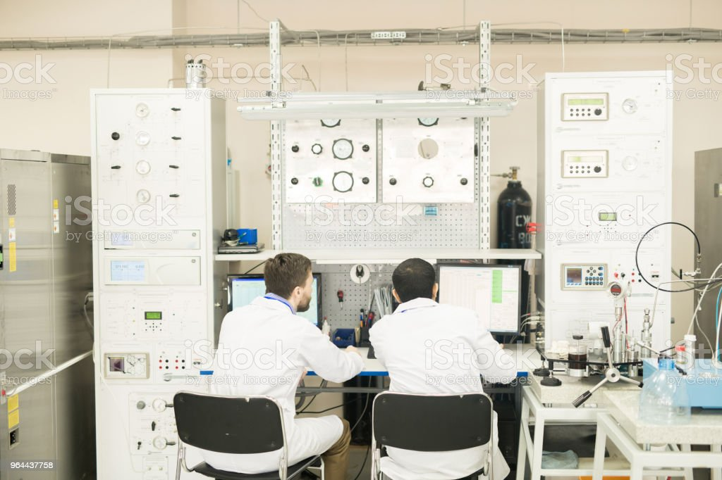 Engineers working with computer connected to control cabinet - Royalty-free Adult Stock Photo
