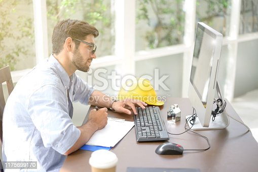 944992706istockphoto Engineers working within an office using a computer. He put the helmet on the side 1175699170