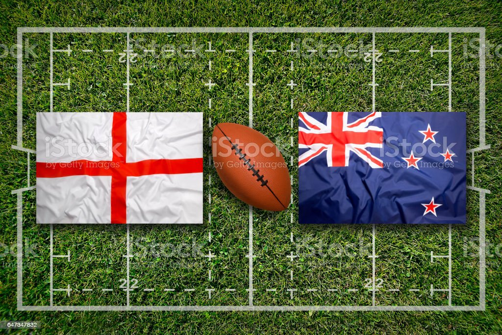England vs. New Zealand flags on green rugby field