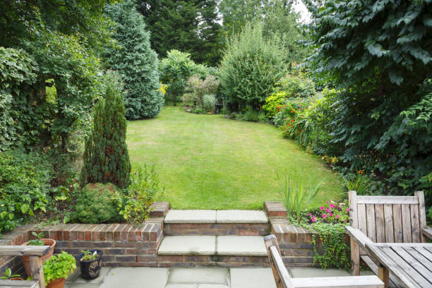 English back garden Terraced and landscaped back garden in England UK with patio, grass and stone steps backyard stock pictures, royalty-free photos & images