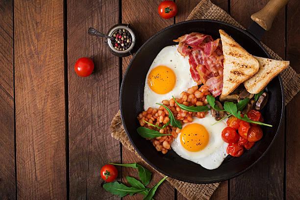 englisches frühstück-spiegelei, bohnen, tomaten, frühstücksspeck und toast. - gefüllte eier stock-fotos und bilder