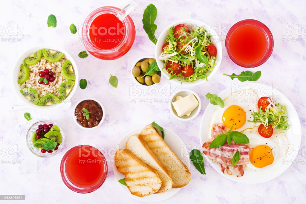 English breakfast - fried egg, tomatoes and bacon. Breakfast for two. Oatmeal. Flat lay. Top view royalty-free stock photo