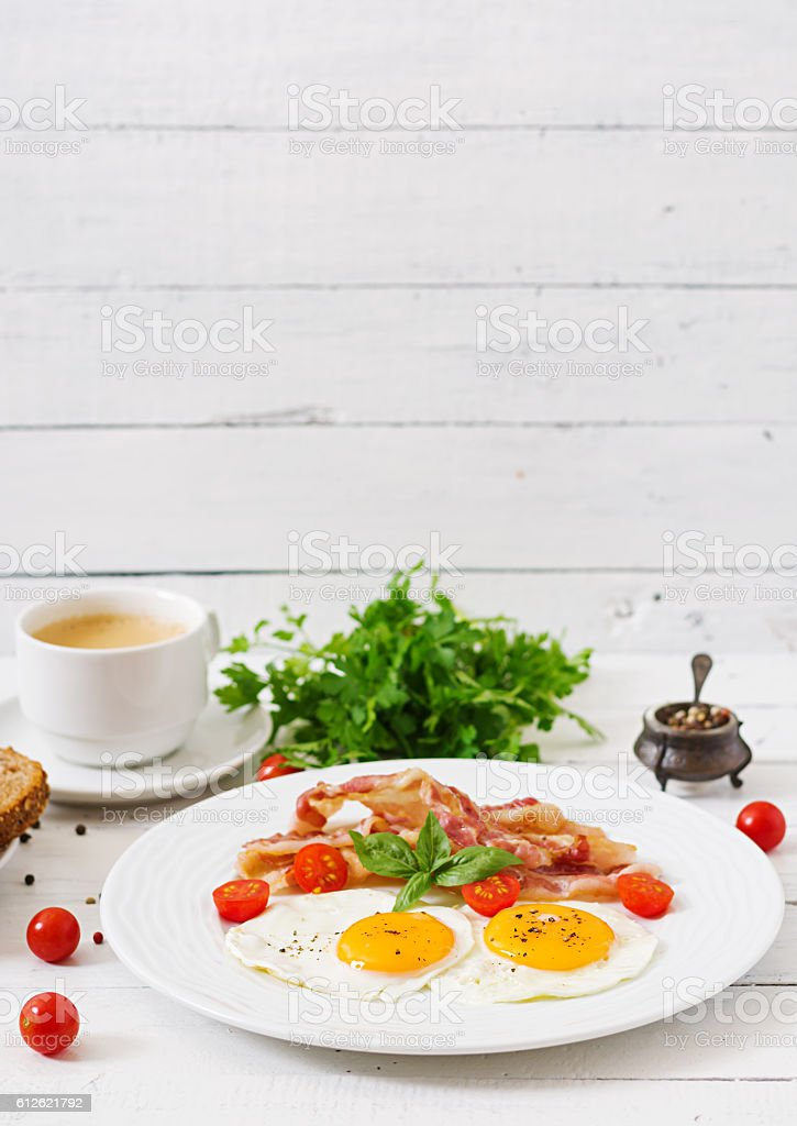 English breakfast - fried egg, tomatoes and bacon. stock photo