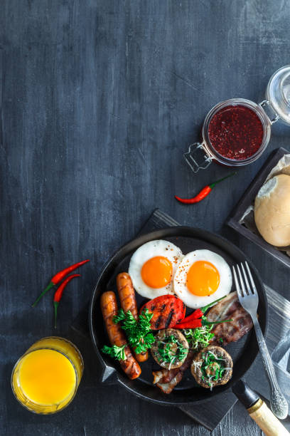 English Breakfast in a pan with fried eggs, sausages, bacon, mushrooms, jam and orange juice on dark stone background copy space, top view flatlay stock photo