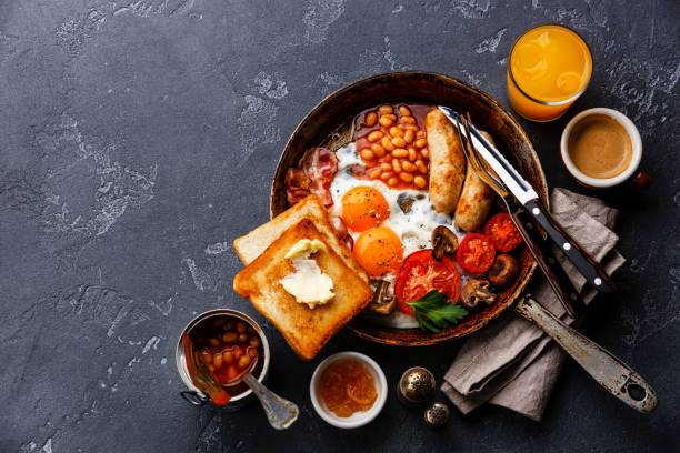 english breakfast in cooking pan - gefüllte eier stock-fotos und bilder