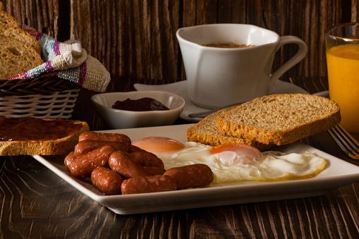 Huevos fritos, salchichas y tostadas con café con leche y zumo de naranja.