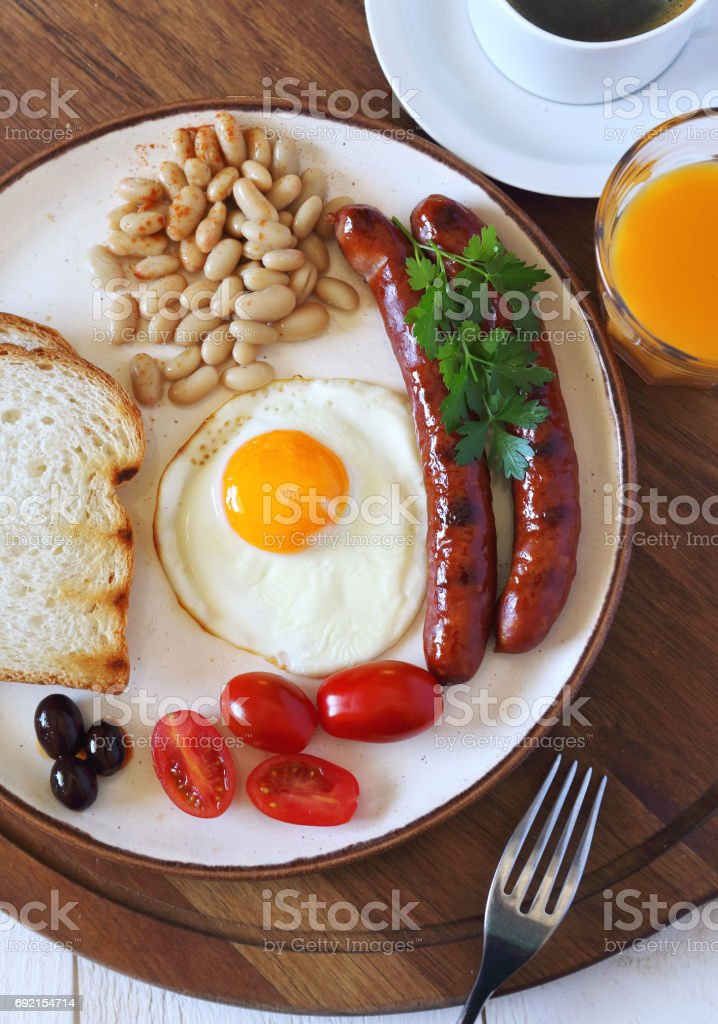 English breakfast: sausage, fried egg, baked beans and coffee stock photo