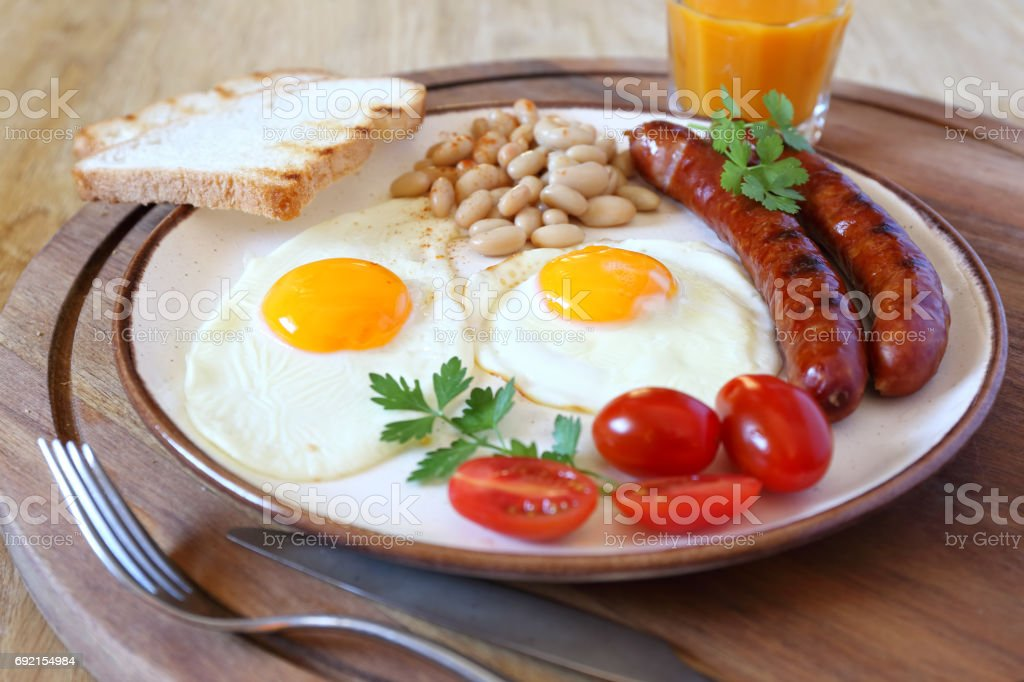 English breakfast: sausage, fried eggs, and juice stock photo