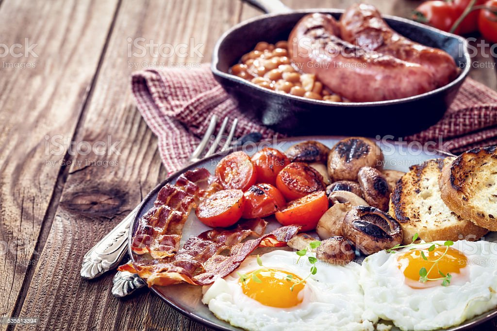 English breakfast with eggs, tomatoes, mushrooms, bacon, beans stock photo