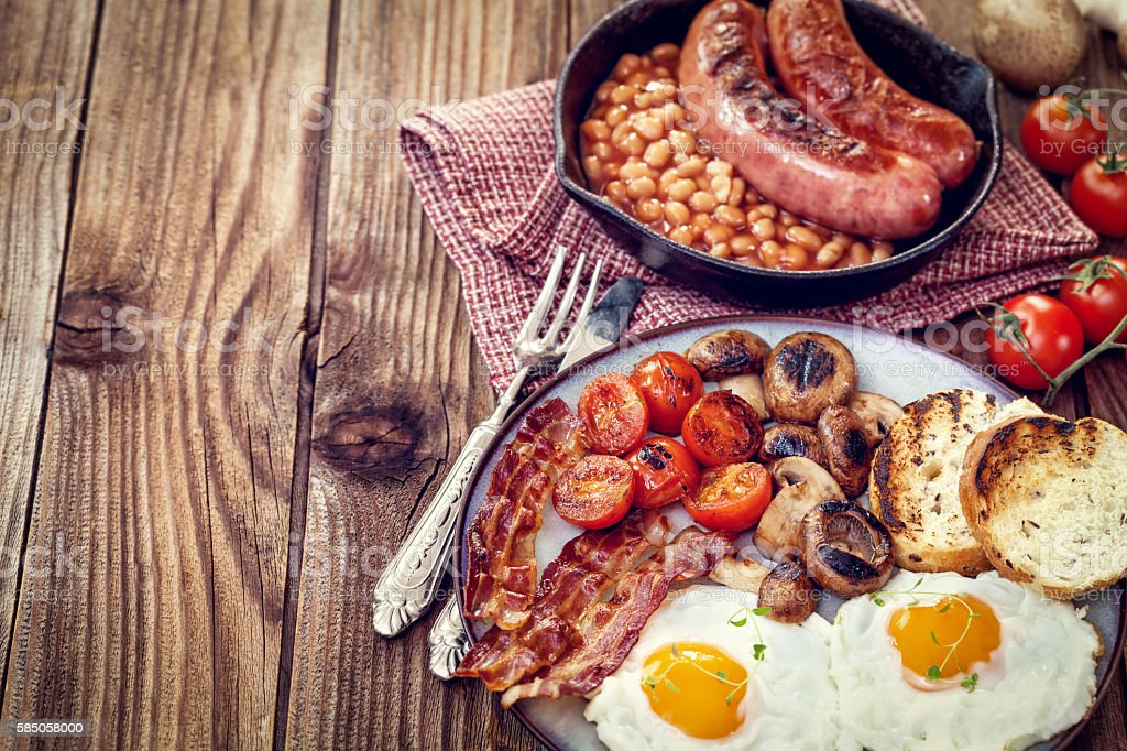 English breakfast with eggs, tomatoes, mushrooms, bacon, beans... stock photo