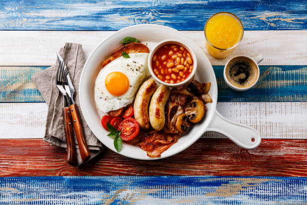 english breakfast with fried eggs, sausages, bacon, beans, toast, orange fresh and coffee - confiture tomatoes imagens e fotografias de stock