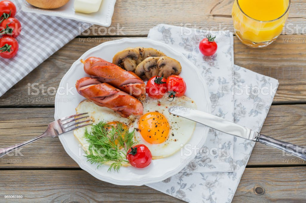 English breakfast with fried eggs, sausages, mushrooms, grilled tomatoes zbiór zdjęć royalty-free