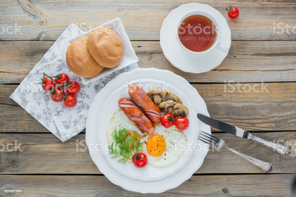 English breakfast with fried eggs, sausages, mushrooms, grilled tomatoes royalty-free stock photo