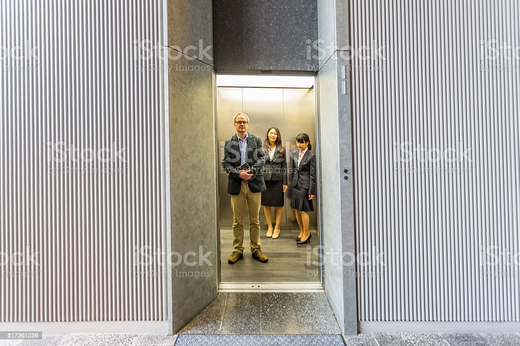 English Businessman With Japanese Corporate Professional Women in Office Elevator – Foto