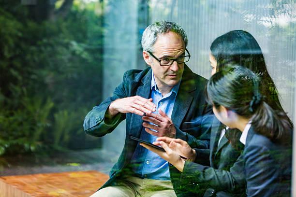 English Businessman Working Advising Japanese Corporate Professional Business Women ストックフォト