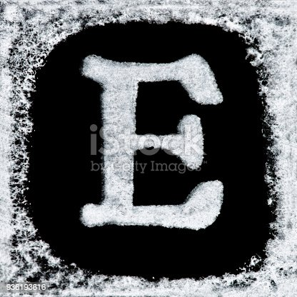 istock English capital letter 'E' printed white ink stamp isolated on black background. Cut out. 936193616