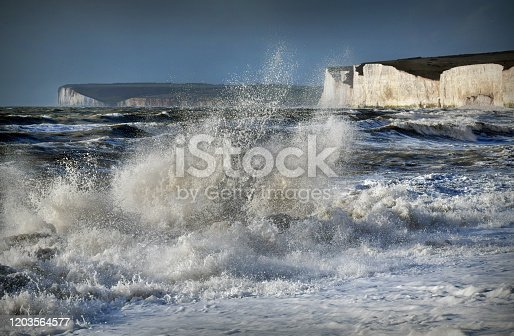 Dramatic waves in the English Channel set against the majestic white cliffs known as the Seven Sisters. Birling Gap, East Sussex, UK