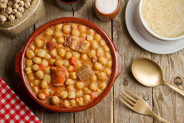 Spanish Cocido Spanish Cocido in an earthenware pot and soup in a white bowl on a wooden table cooked stock pictures, royalty-free photos & images