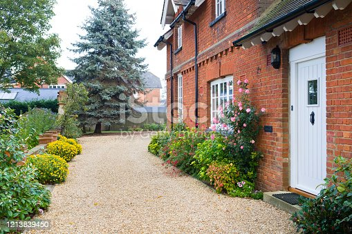 English country house and garden in Autumn with a gravel driveway. The house is Victorian period, with flower borders filled with shrubs and perennials
