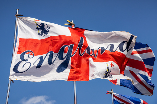 The Saint George's Cross flag in the wind, with the word 'England' superimposed.