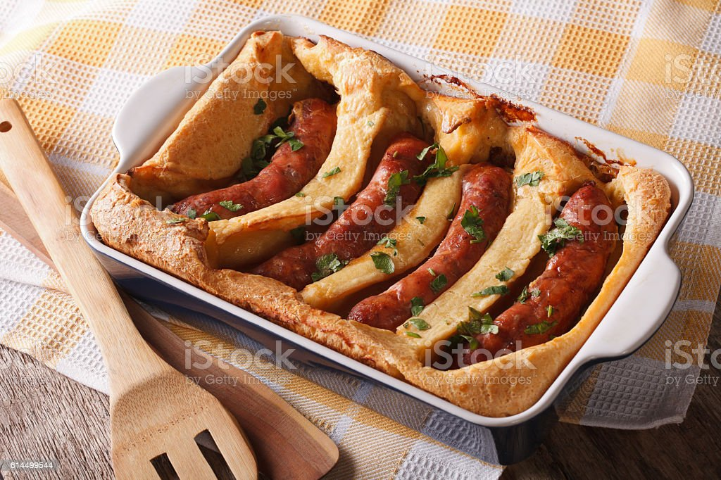 English food: toad in the hole into baking dish closeup stock photo