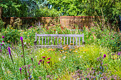 Lovely English Garden on a summer day with a wooden bench surrounded by wildflowers and trees