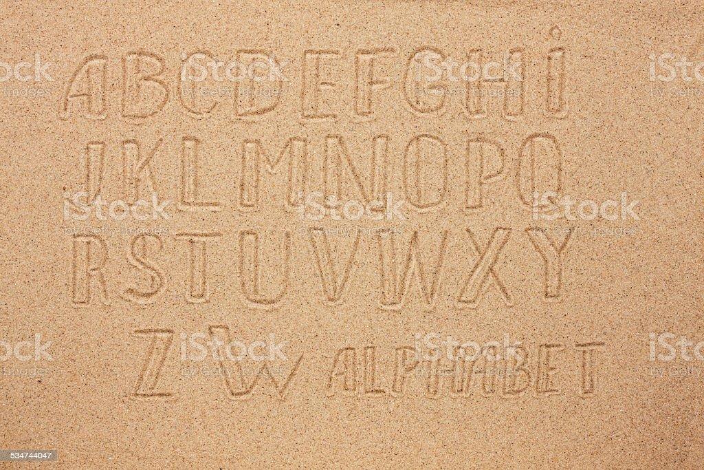 English, German, Portuguese alphabet  written on the sand stock photo