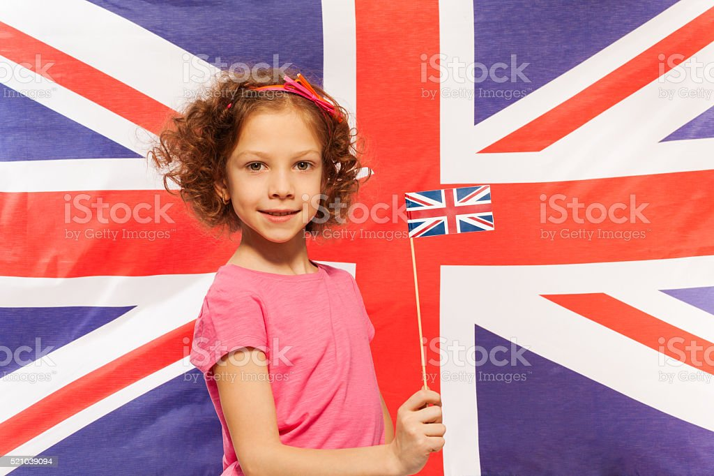 English girl with flag in front of British banner stock photo