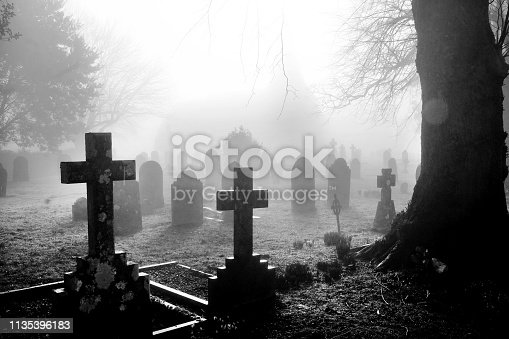 An english grave yard in the mist, in the foreground the head stones are in the shape of Christian crosses the head stones become more shrowded in mist and fog a distant dark shape of the church can be seen in the background, black and white photograph has a horror film feel about it.