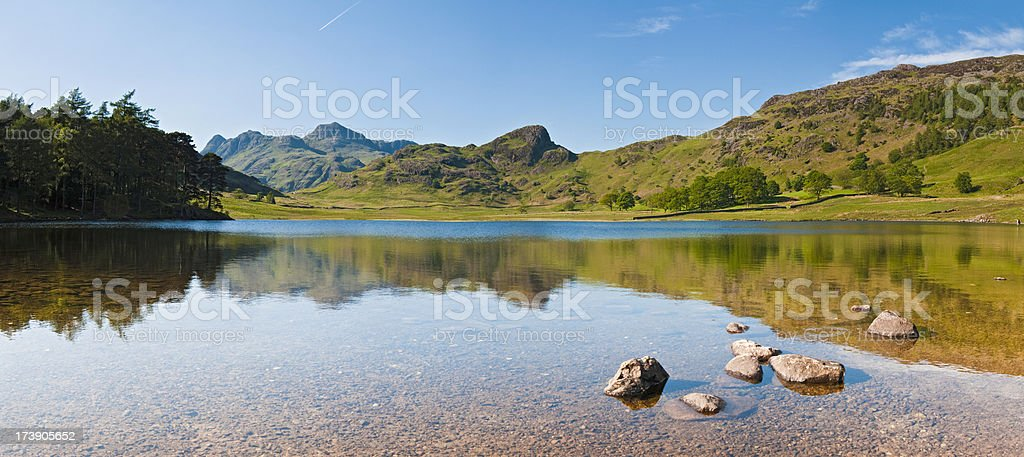 English Lake District tranquil mountain tarn reflected panorama stock photo