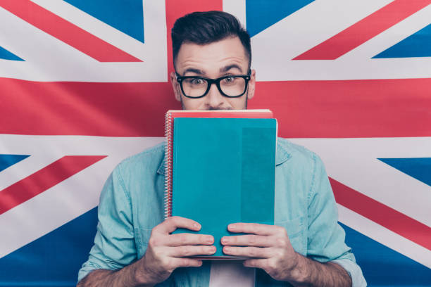 English language learning concept-portrait of excited man holding colorful copy books in hands closing half face with notebooks standing over English flag background stock photo