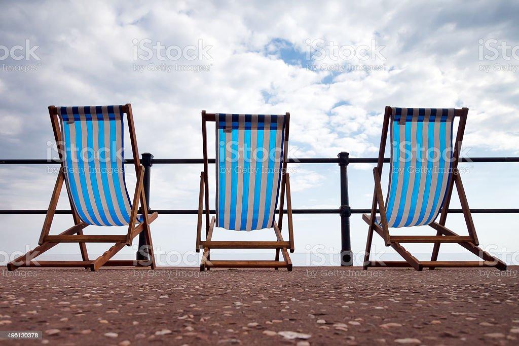 English seaside summer, bad weather. Deserted deckchairs,nobody. stock photo