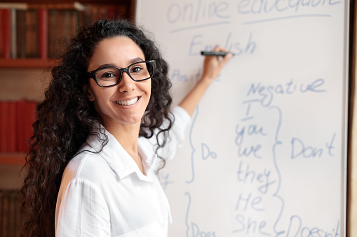 Education And Learning Concept. Portrait of smiling female teacher standing at whiteboard, explaining grammar rules to students. Excited woman in glasses looking at camera, writing on the board
