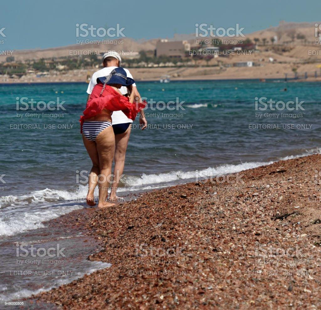 Englische Touristen zu stampfen, ohne Schuhe durch den Kies – Foto