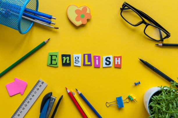 Palabra inglesa de letras talladas sobre fondo amarillo con oficina o escolares, concepto de aprendizaje del idioma inglés - foto de stock