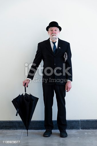 Englishman in bowler hat and  black umbrella and fold newspaper .
