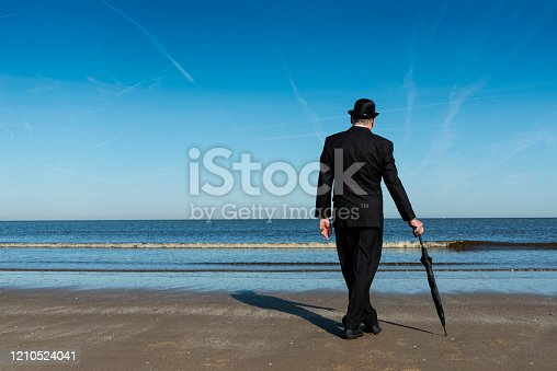 Englishman with bowler hat and umbrella stands  on the beach overlooking the sea and towards Europe.