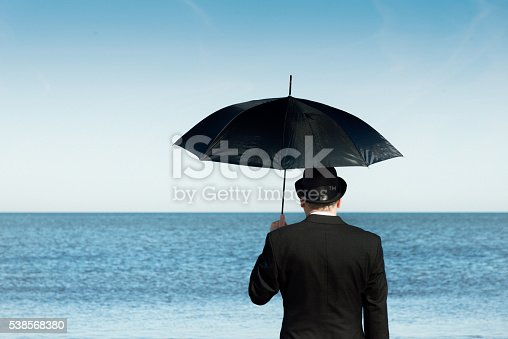 Englishman with bowler hat and umbrella  on the beach overlooking the sea and towards Europe.