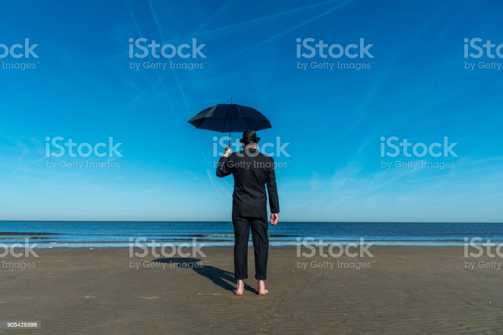Englishman with bowler hat and umbrella stands barefoot on the beach overlooking the sea and towards Europe.'nConcept for the Brexit referendum. stock photo