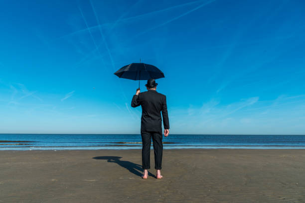 Englishman with bowler hat and umbrella stands barefoot on the beach overlooking the sea and towards Europe.